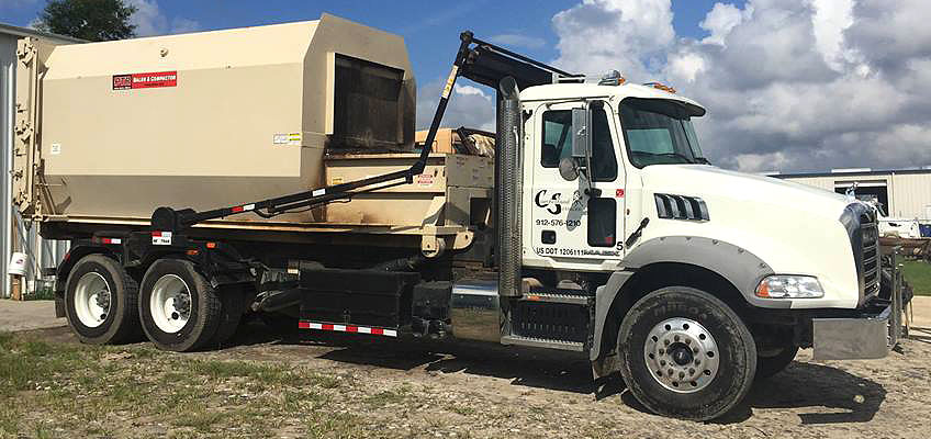 Cumberland Services Customized Compactor on roll-off truck