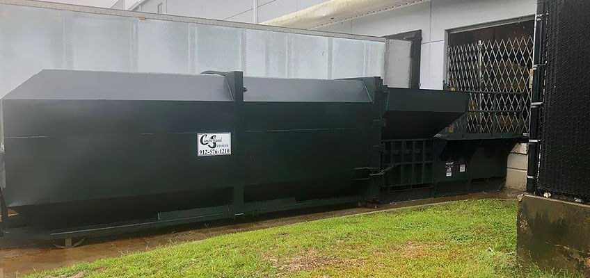 Cumberland Services LLC compactor with integrated loader